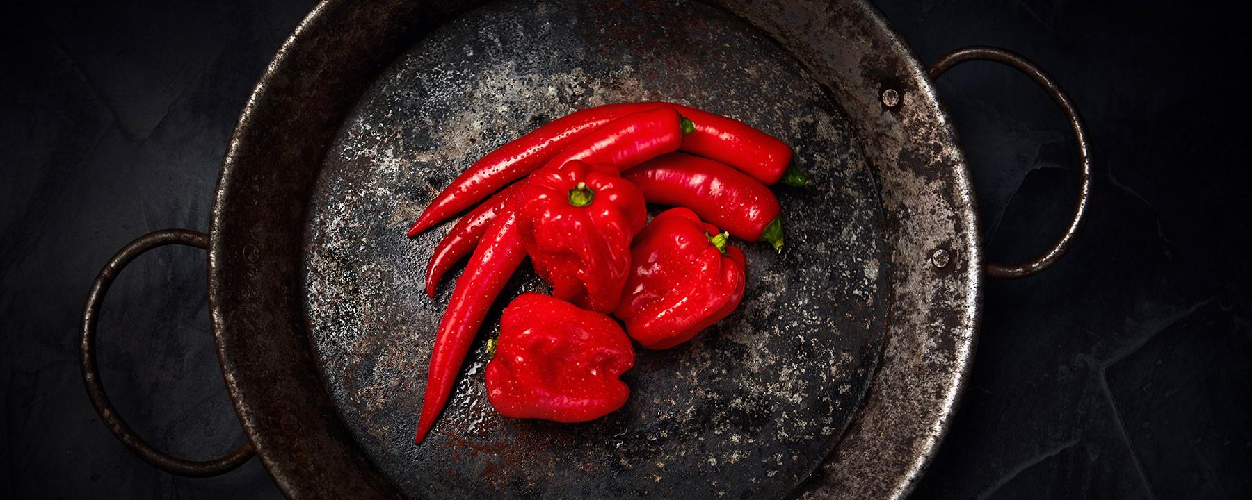 Produkt-Fotografie von roten Chilis und Habaneros in einer Pfanne.